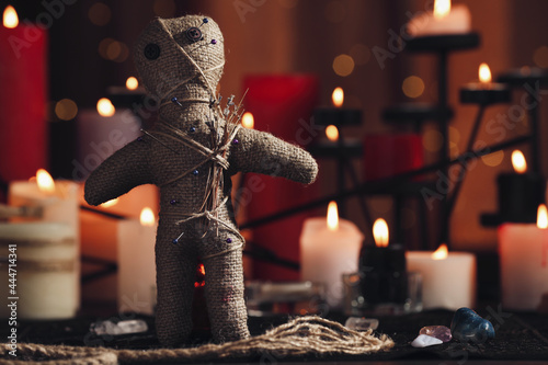 Fotografiet Voodoo doll with pins and dried flowers on table in room, space for text