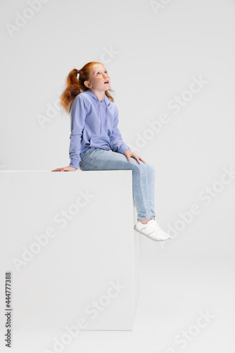 Stampa su Tela One cute red-headed girl in casual clothes sitting on big box isolated on white studio background