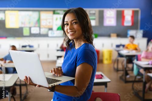 Fotografie, Obraz Portrait of african american female teacher holding laptop in the class at schoo