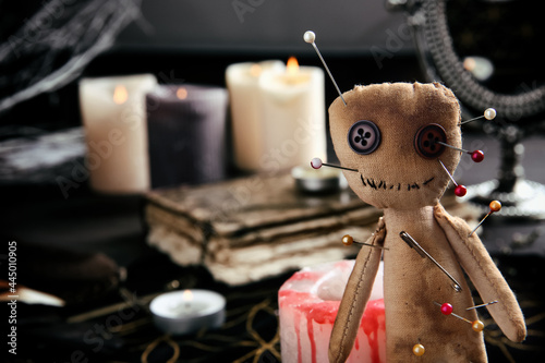Fotografia Voodoo doll pierced with pins on table indoors, closeup