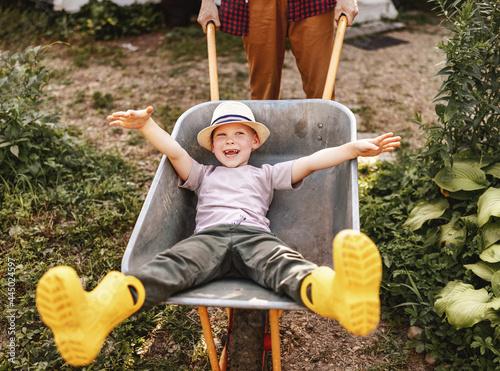 cheerful child boy laughs in a garden wheelbarrow in the summer Fotobehang
