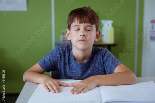 Blind caucasian schoolboy sitting in classroom with eyes closed reading braille book with fingers