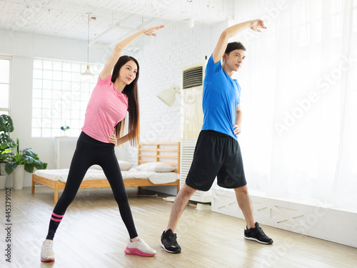 Foto Young couple doing  lateral flexion exercise at home.