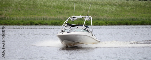 Fotografie, Obraz White powerboat with towing targa fast float on calm river water on green grassy