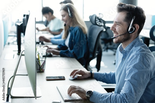 Canvastavla Young handsome male customer support phone operator with headset working in call