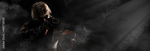 Fotografia US Army soldier in combat uniforms holding machine gun ready to attack in smoke around on dark background