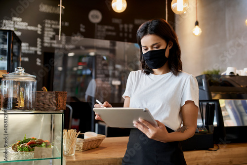 Photo Female cafe owner, entrepreneur using digital tablet