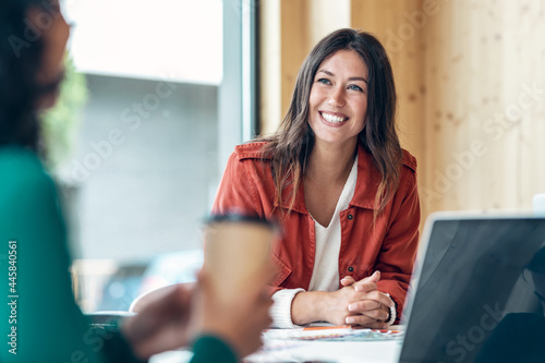 Tableau sur Toile Smiling young business woman listening her partner on coworking space