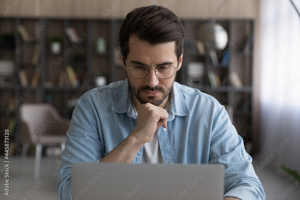 Leinwandbild Motiv - fizkes : Thoughtful young male manager in eyeglasses looking at laptop screen, considering problem solution, preparing research report, analyzing sales statistic, developing strategy, working on online project