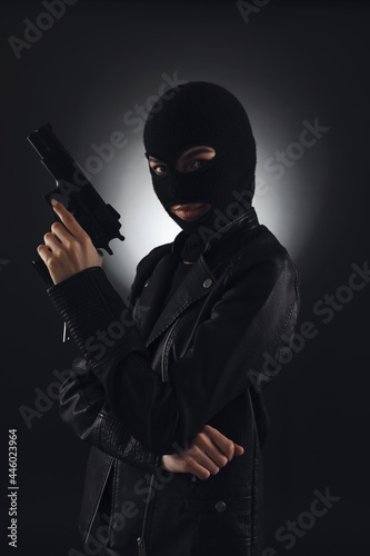Wallpaper Mural Woman wearing knitted balaclava with gun on black background