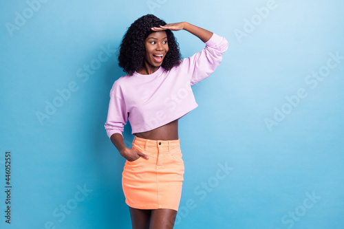 Portrait of attractive cheerful curious slim girl looking far away meet friend isolated over bright blue color background