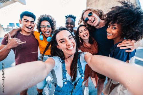 Billede på lærred Multicultural happy friends having fun taking group selfie portrait on city stre