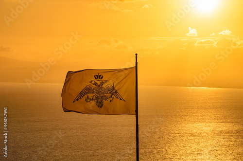 Fotografija The Byzantine empire flag waving over the Messenian Gulf against the yellow sky at sunset