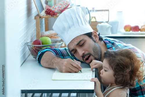 Fototapeta Chef and daughter discuss today's menu in his kitchen