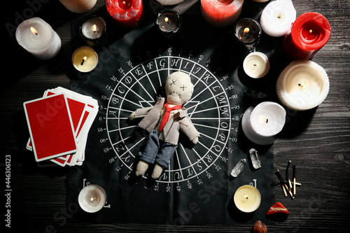 Canvastavla Voodoo doll pierced with needle surrounded by ceremonial items on table, flat la