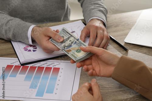 Fotografía Cashier giving money to businesswoman at desk in bank, closeup