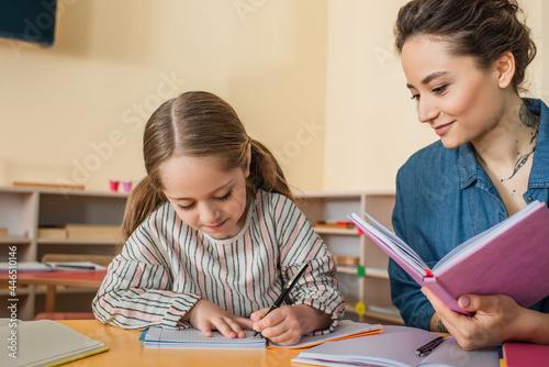 Obraz na płótnie happy teacher smiling near concentrated girl writing dictation in montessori sch