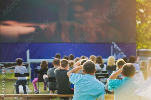 Fototapeta A group of people watching an open-air cinema screen