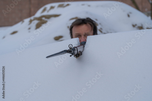 Foto Man and soviet Mosin rifle with a bayonet in a snowy trench in winter