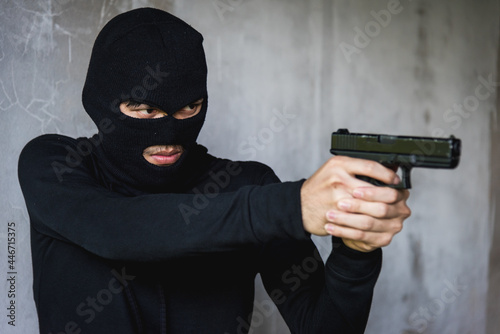 Fotografiet Black dressed man and gun aiming, robber concept