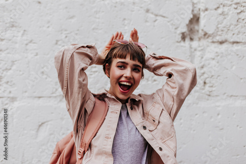 Fototapeta Good-humored girl posing on backdrop of wall