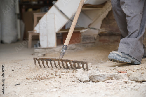 Obraz na plátně Unrecognizable young builder raking the floor at a construction site