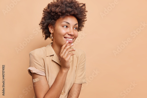 Wallpaper Mural Cheerful Afro American woman with curly hair looks happily away smiles broadly g