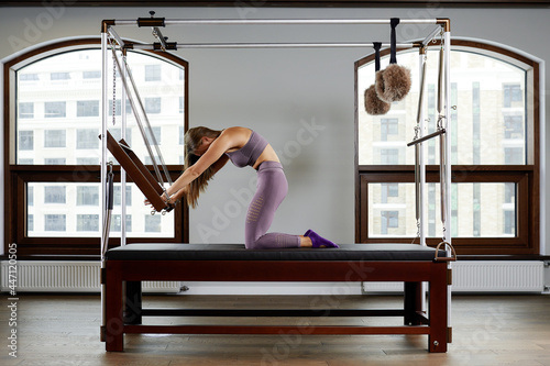 Valokuvatapetti Pilates aerobics instructor woman in fitness exercise on cadillac reformer, musculoskeletal system training on modern reformer simulator