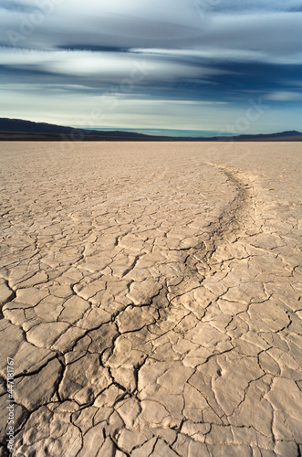 Fotografia dry cracked earth in the desert and mountains background blue sky