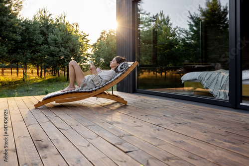 Wallpaper Mural Young woman resting on sunbed and reading on a tablet on the wooden terrace near the modern house with panoramic windows near pine forest