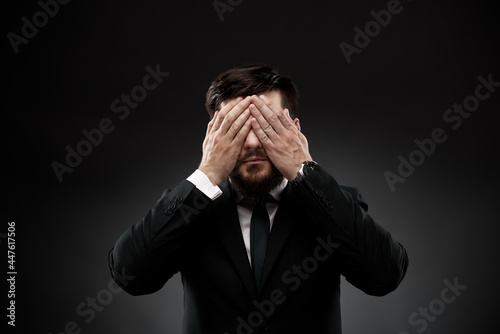 Obraz na plátne Man in suit covering face with hands