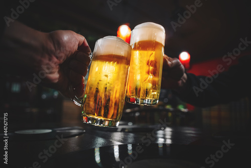 Fotografie, Obraz two glass of beer in hand. Beer glasses clinking in bar or pub