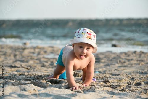 Obraz na płótnie Cute toddler boy at the river coast has fun, summertime leasure