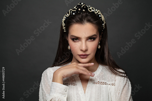 Fotografiet Portrait of a young nice woman with headband in a studio on a black background