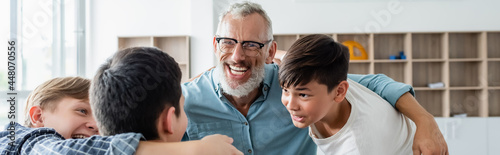Photo multicultural boys and cheerful middle aged teacher embracing in classroom, bann