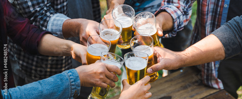 Fotografia Cropped shot of people holding beer glasses celebrating in the summer camping party outdoor