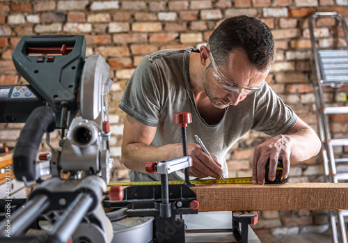 Canvastavla Professional carpenter working with a miter saw.