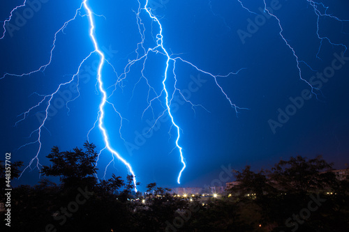 Obraz na płótnie Lightning discharges during a large rainstorm in a city with forest fringes