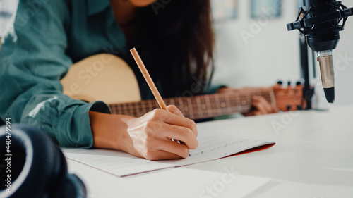 Fotografie, Obraz Happy asia woman songwriter play acoustic guitar listen song from smartphone think and write notes lyrics song in paper sit in living room at home studio