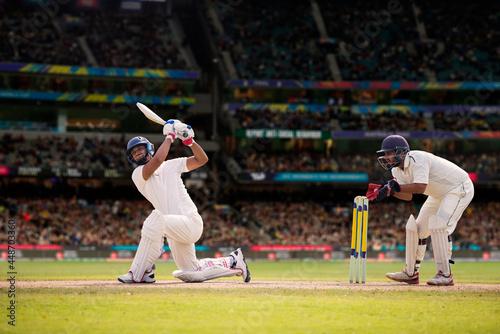 Obraz na plátně Cricketer batsman hitting a shot during a match on the cricket pitch during a ma