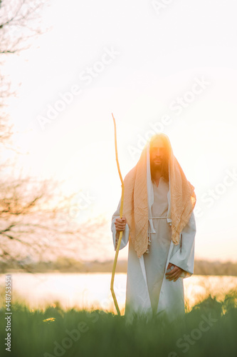 Jesus Christ with wooden staff stands in white robe near river at sunset Fototapeta