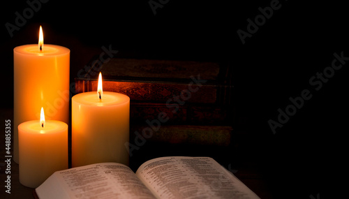 Canvastavla Three Pillar Candles Burning in a Dark Room with a Bible