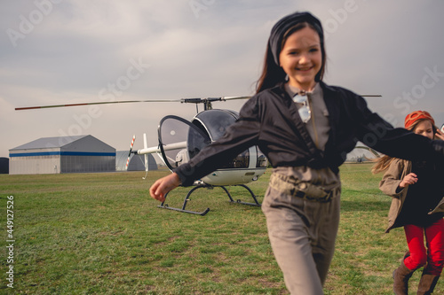 Fotografia Cheerful tween girl running on background of helicopter on airfield