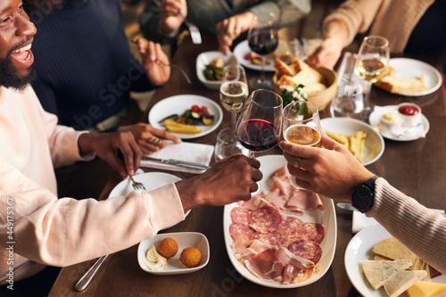Friends toasting at dinner in restaurant Fototapet