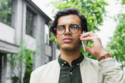 Fotografiet young man in eyeglasses and bomber jacket looking away while talking on smartpho
