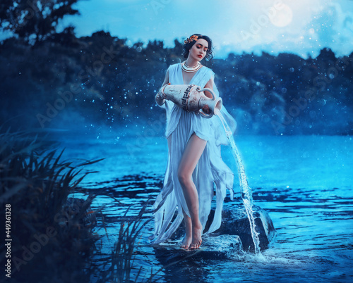 Fotografia Fantasy woman Greek goddess zodiac sign Aquarius holds vintage earthenware jug in her hands and pours water into river