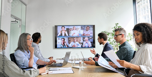 Photo Diverse company employees having online business conference video call on tv screen monitor in board meeting room