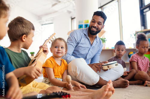 Fotografie, Obraz Group of small nursery school children with man teacher sitting on floor indoors in classroom, playing