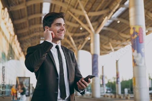 Valokuva Bottom view friendly traveler businessman man in black dinner suit earphones sta