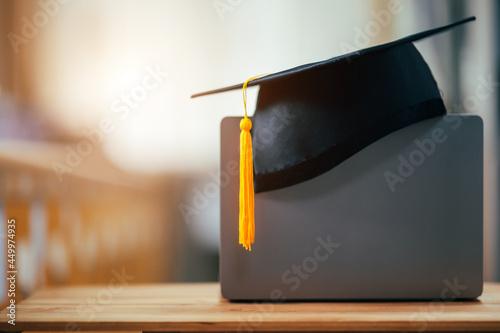 Fototapeta black graduation cap with yellow tassels put on laptop